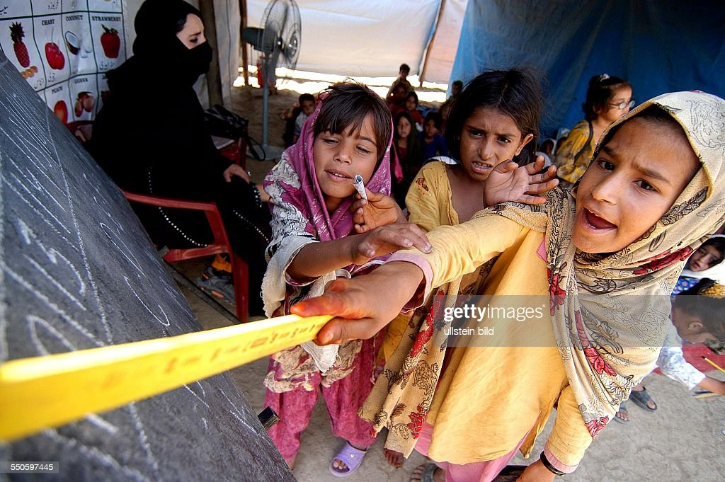 SHEICK SHAZAD CAMP, MARDAN, SARHAD PROVINCE, PAKISTAN - JUNE 24TH: Three young Pashtun refugee girls are reading from a black baord various sentences and words for the rest of the class, June 24th 200 : News Photo
