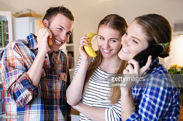 Three young people having fun using fruit as telephones