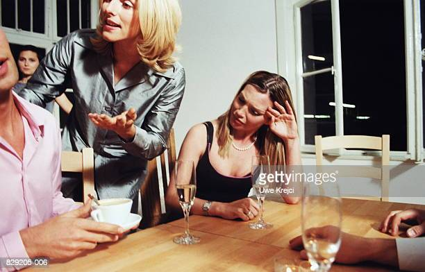 Three young people having serious discussion at dinner party