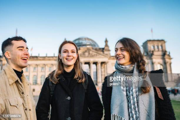 three young people in front of berlin reichstag - central berlin stock photos and pictures