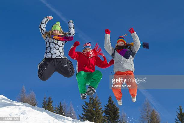 Three young people in winter clothes jumping downhill on snow