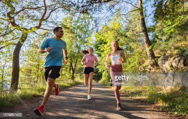 drie jonge mensen die samen in aard joggen. - running stockfoto's en -beelden