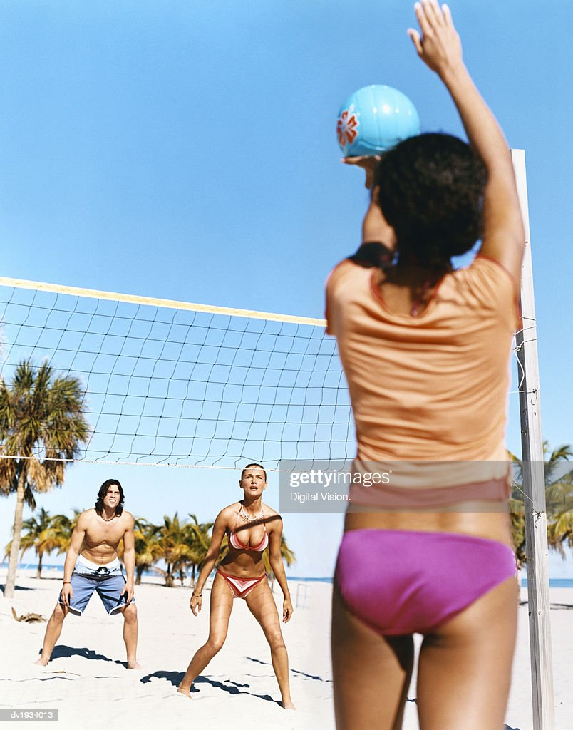 Three Young People Playing Volleyball on a Beach : Stock Photo