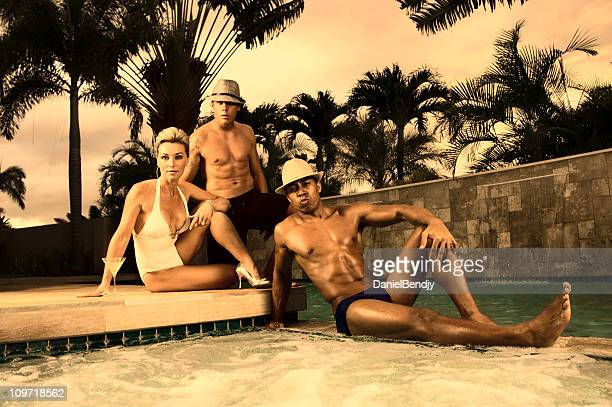 three young people relaxing near pool, toned - black men in speedos stock photos and pictures