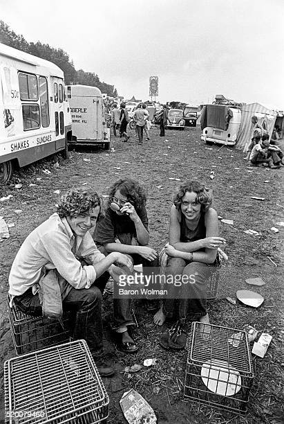 Three young people rest in the car park at the Woodstock Music Art Fair Bethel NY August 15 1969