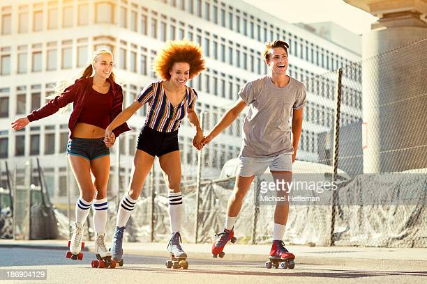 three young people rollerskating