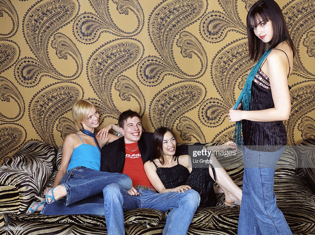 Three Young People Sitting on a Zebra Print Sofa Laugh at Their Friend, Showing Off : Stock Photo