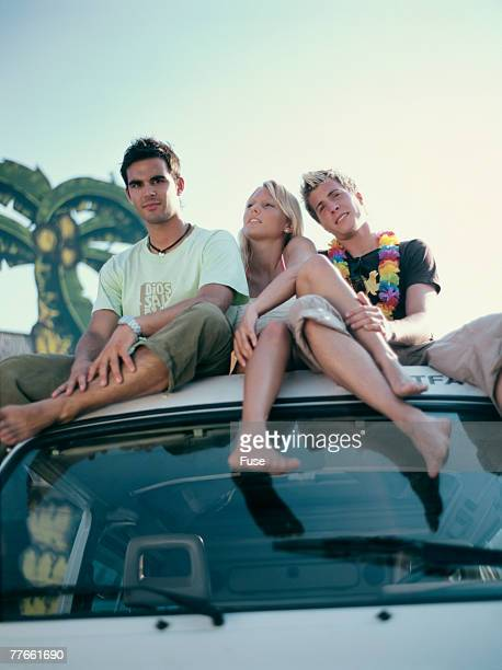 Three young people sitting on roof of a mini van
