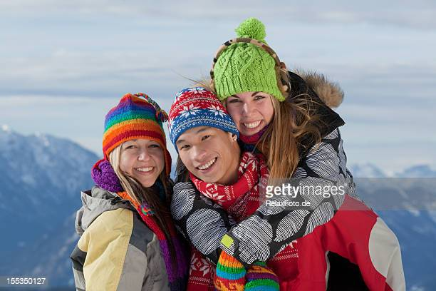 Three young people standing on mountain peak in winter