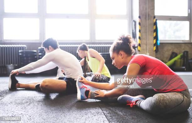 three young people stretching in gym - warm up exercise stock pictures, royalty-free photos & images