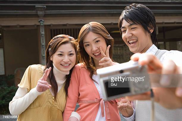 Three young people taking a picture of themselves, front view, Japan