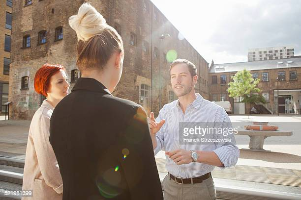 Three young people talking, building in background, East London, UK