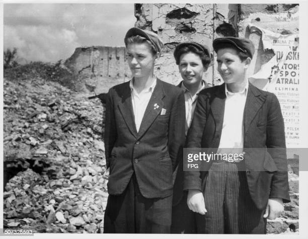 Three young Polish men standing in the ruins of Warsaw during World War Two Poland circa 1945
