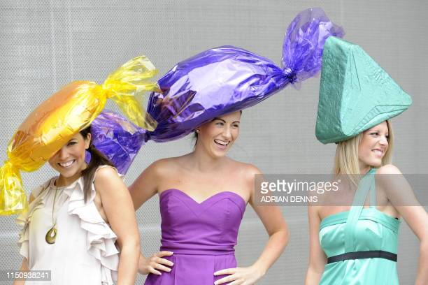 Three young racegoers pose with their hats designed as Quality Street chocolates during Ladies Day the third day of Royal Ascot in Berkshire west of...