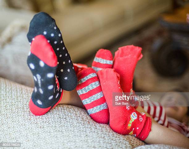 three young siblings relaxing on sofa, feet raised, focus on feet - girls in socks stock photos and pictures