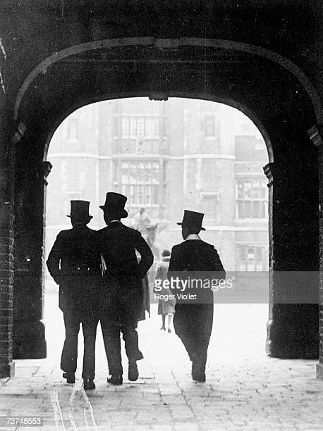 Three young students in tail coats and top hats walk under an archway as they enter the grounds of Eton College Eton England late 1920s Formally...