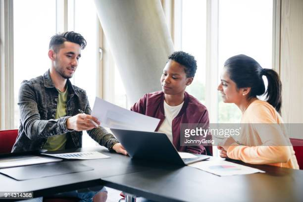three young students looking at document with laptop in classroom - learn english stock pictures, royalty-free photos & images
