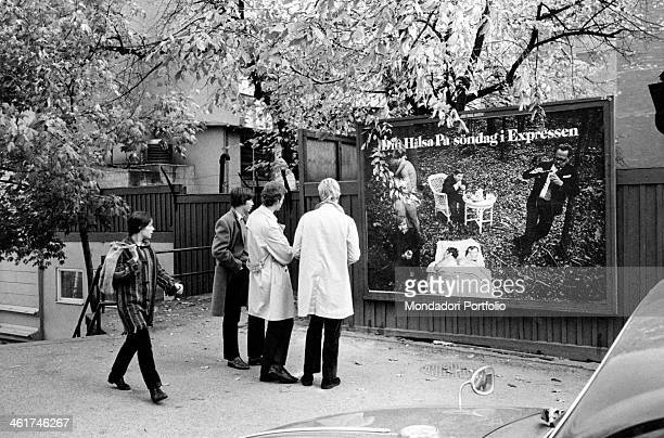Three young Swedish university students observing a placard Stockholm 1969