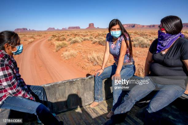 three young teenage navajo sisters riding in the bed of a pickup wearing covid-19 masks to flatten the curve and stop the spread of the corona virus - cherokee indian women stock pictures, royalty-free photos & images