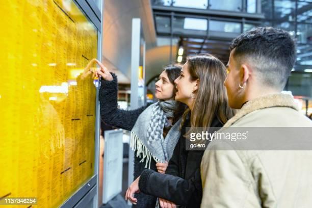 drei junge reisende prüfen zugverbindung am fahrplan - bahnreisender stock-fotos und bilder