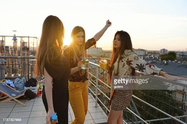 tres mujeres jóvenes bebiendo cócteles al aire libre - casual chic fotografías e imágenes de stock