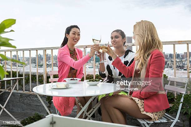 three young woman having a drink on city roof