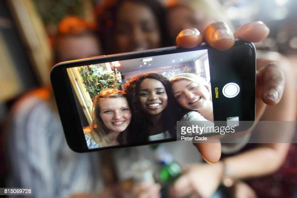 three young woman in bar taking photo of themselves - only young women stock pictures, royalty-free photos & images