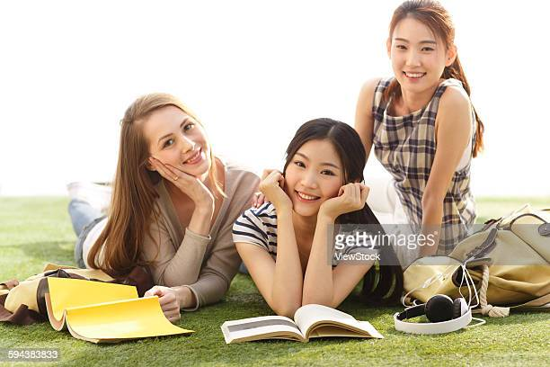 Three young woman lying on lawn reading