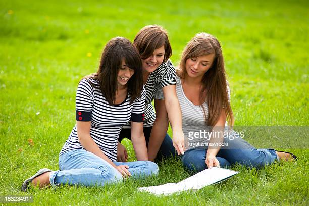 Three young woman reading book