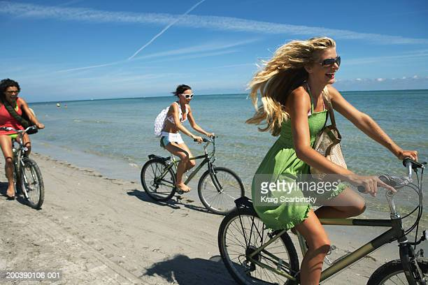 Three young woman riding bicycles on beach, laughing, side view