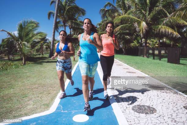 three young woman running outdoors