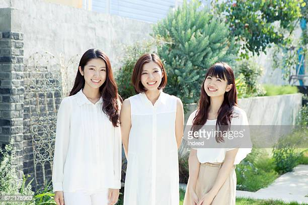 three young woman smiling at backyard - three people ストックフォトと画像