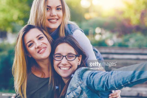 Three young woman taking a selfie outdoors
