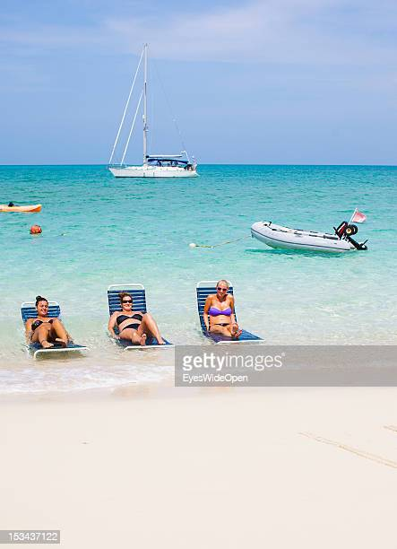 Three young woman tourists in a bikini are taking a sunbath while lying on sunbeds in the turquoise blue water of the caribbean sea at the white...