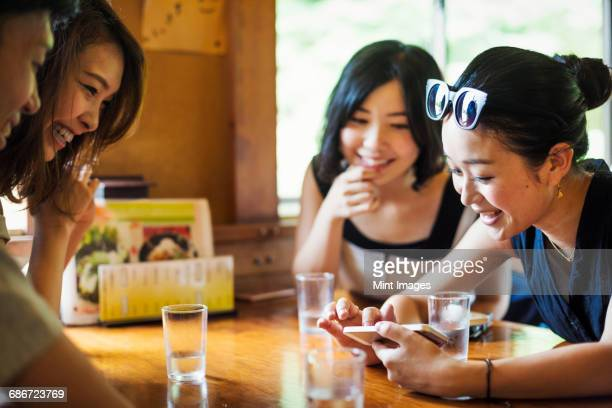 Three young women and a man sitting in a cafe.