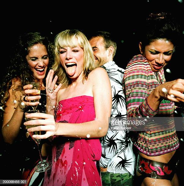 Three young women and man in spray of champagne