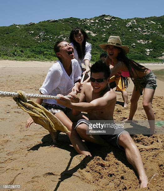 Three young women and two young men playing tug-of-war on the beach