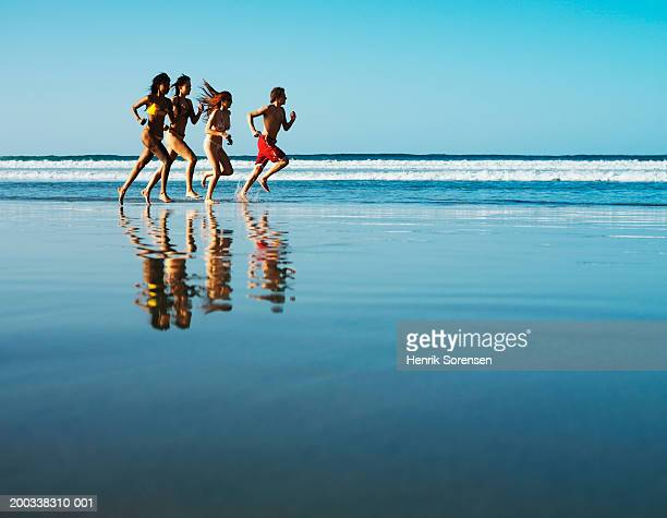 Three young women and young man running on beach