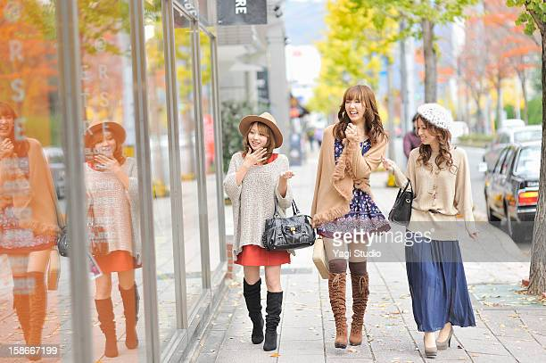 Three young women are walking in the city
