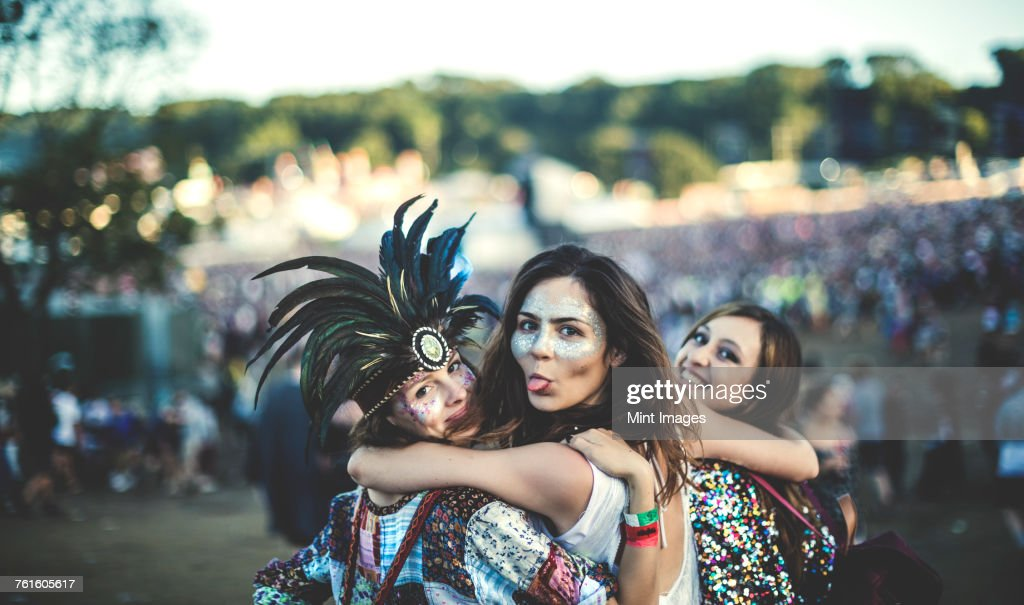 Three young women at a summer music festival feather headdress and faces painted, smiling at camera, sticking out tongue. : Stock Photo