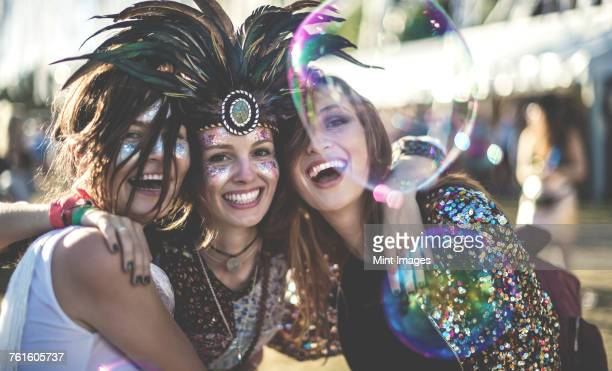 Three young women at a summer music festival wearing feather headdress and faces painted, smiling at camera.