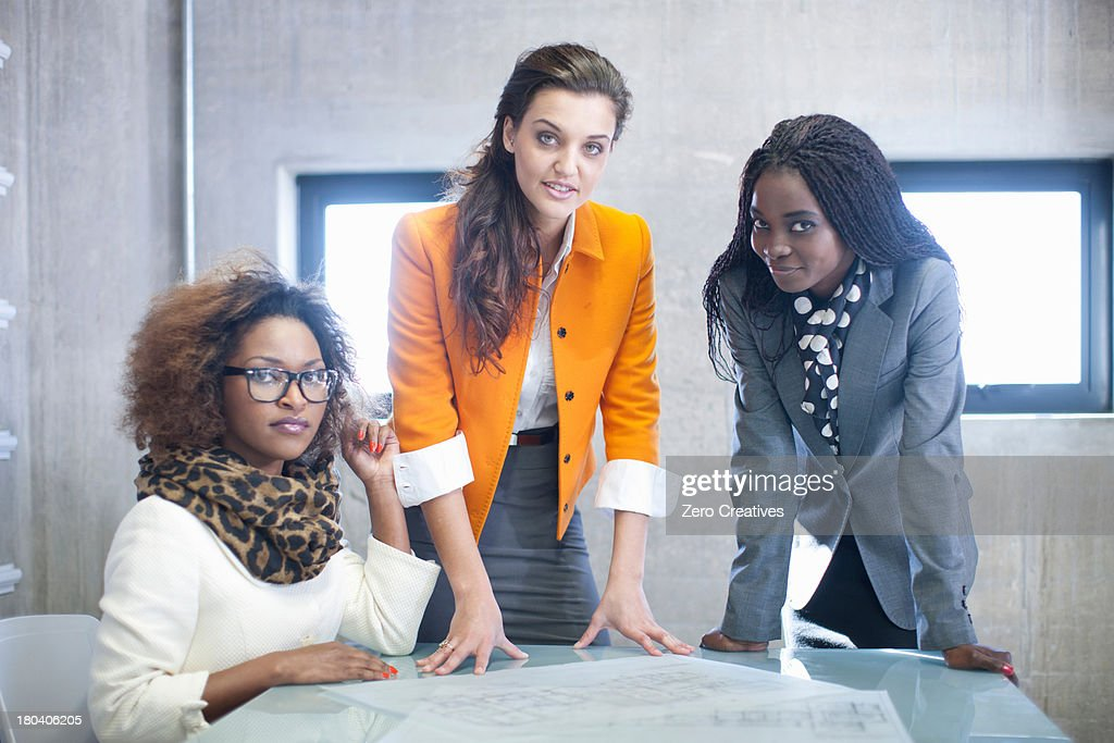 Three young women at desk with blueprint : Stock Photo