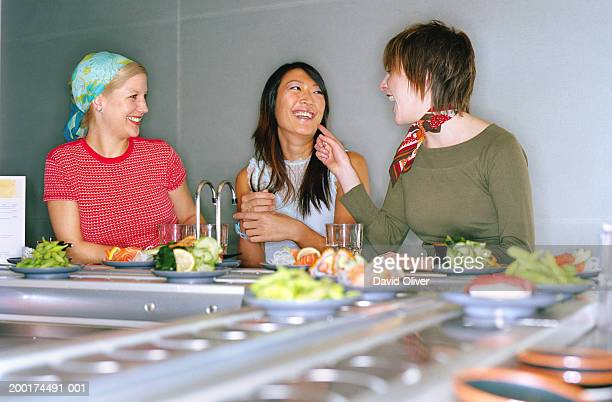 Three young women at sushi bar, laughing