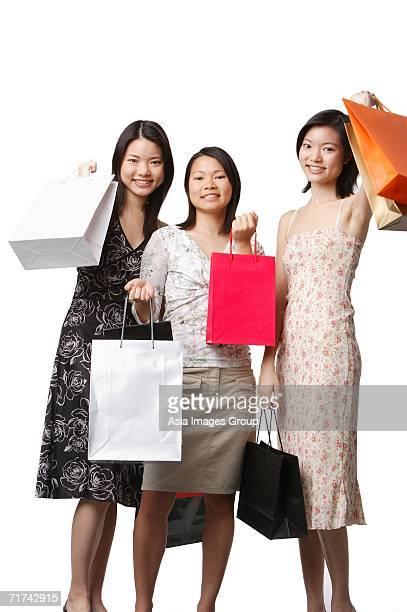 Three young women carrying shopping bags