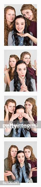 Three young women creating photo booth series of images in filmstrip format