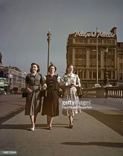 Three young women crossing a bridge in London 1951