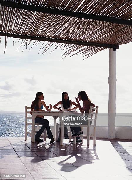Three young women dining on bungalow terrace overlooking ocean