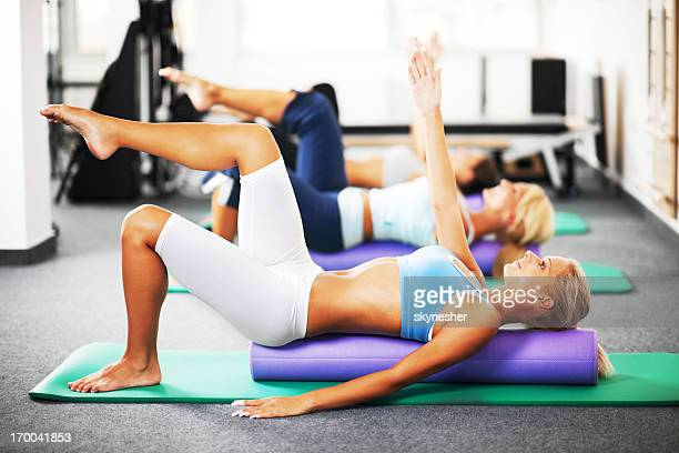 Three young women doing Pilates exercises with a roller.