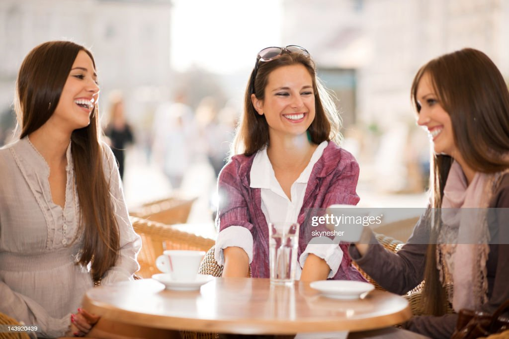 Três jovens mulheres beber café em um café. : Foto de stock