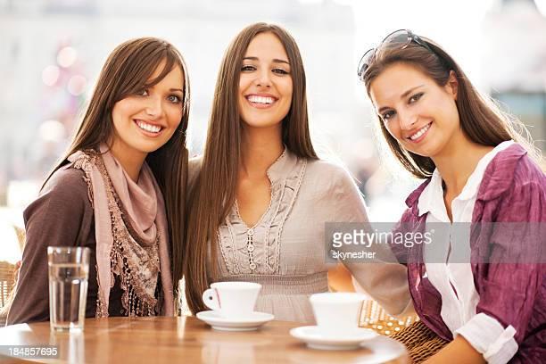 Três jovens mulheres beber café em um café.
